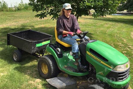 Garden Mentors founder driving John Deere lawn mower tractor